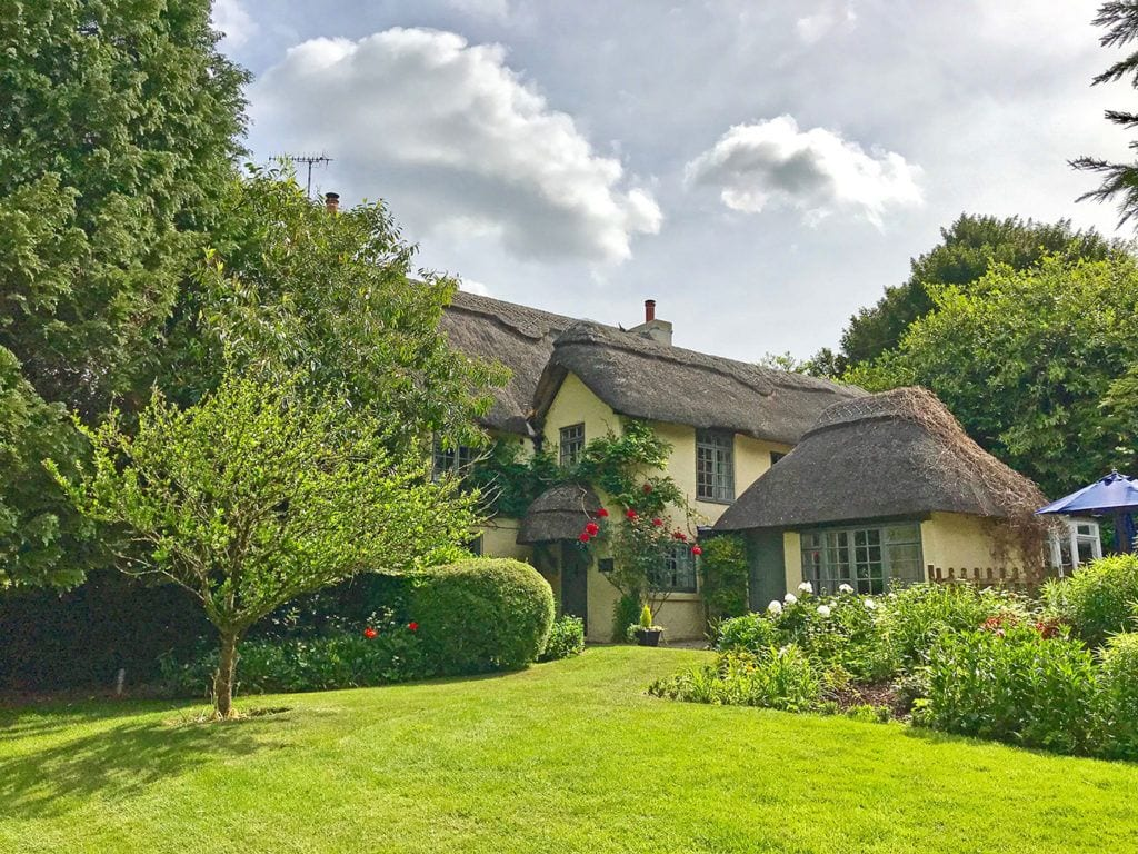Beck Cottage self catering holiday home in the New Forest beautiful roses and wisteria surround this thatch cottage