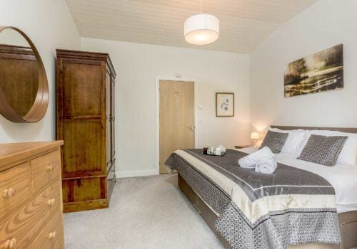 Riverside Lodge bedroom with quirky furniture, neutral colour scheme creating a light and airy atmosphere