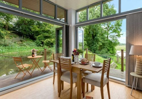 Bi-fold doors to verandah bring the outside in at Riverside Lodge self catering cottage in the New Forest