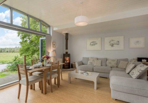 Lounge with bi-fold doors to verandah with dining table and log burner