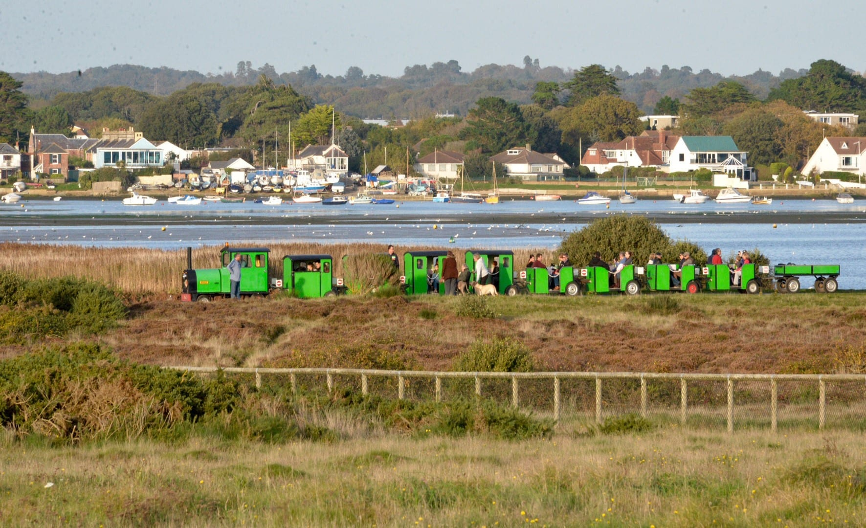 Hengistbury Head train with sailing boats and houses in the background