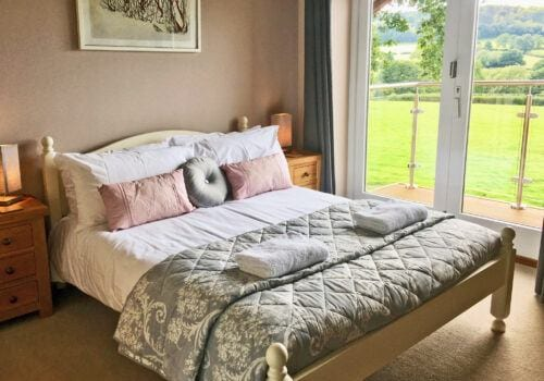 Master bedroom with balcony and ensuite in holiday let in Devon