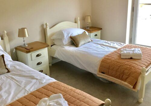 Matching twin beds with fresh white linen in Devon self catering home