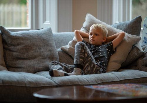 Child relaxing wathcing TV on a sumptiuos couch