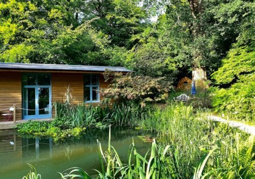 Idyllic scene showing a riveside Lodge and Glamping Pod