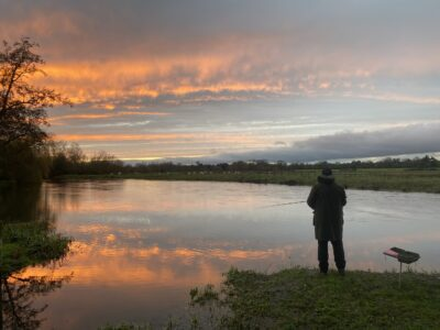 A solitary angler stands with his fishing rod in the sunset on a river