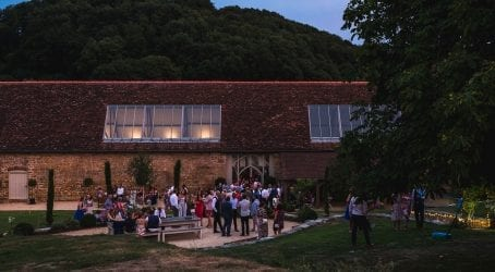 guests outside the tithe barn at a wedding