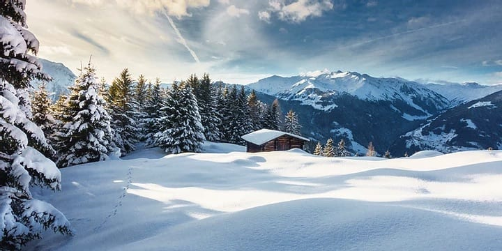 A wooden cabin on a snowy mountain.
