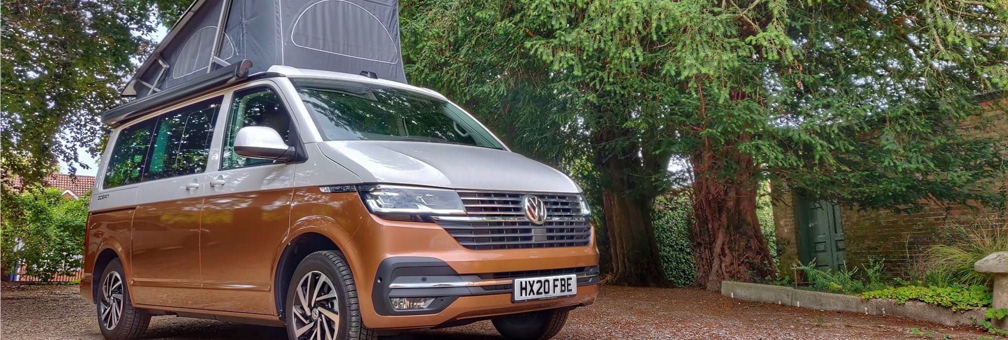 A brown and white, two tone VW campervan, parked in a forest car park.