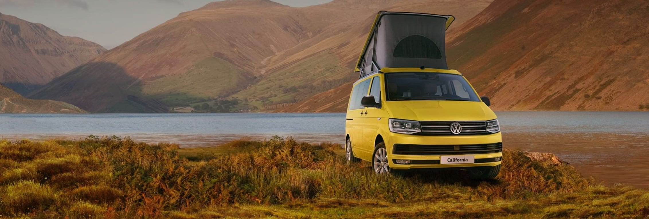A yellow VW California campervan parked in front of a lake and mountain range.