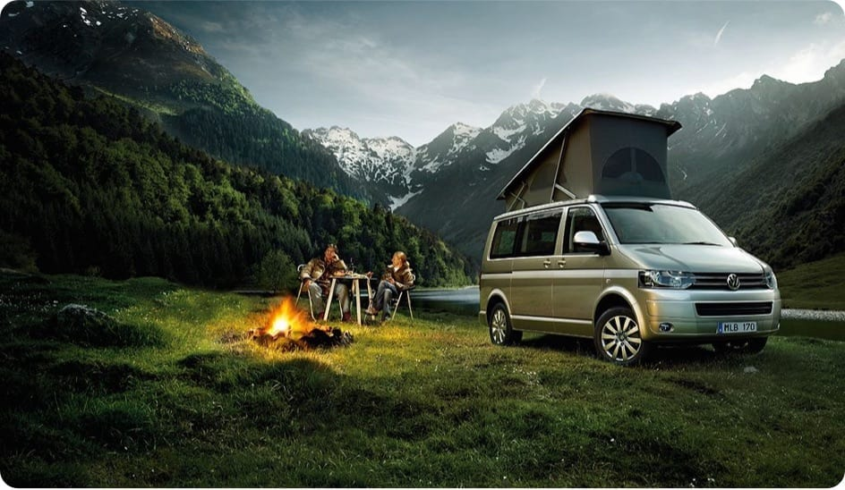 A VW campervan parked infront of some mountains with 2 people sitting infront of a campfire.