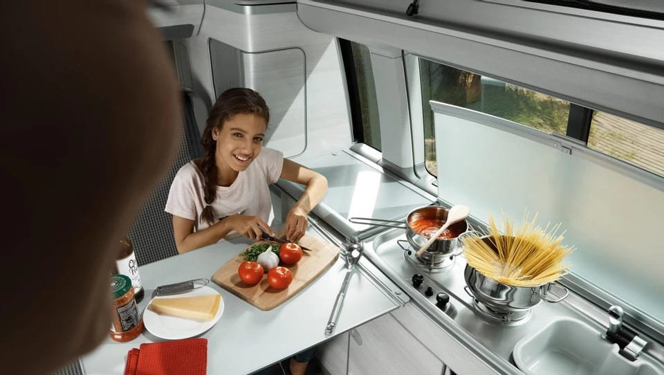 A woman and a girl chopping up some tomatoes inside of a campervan kitchen.