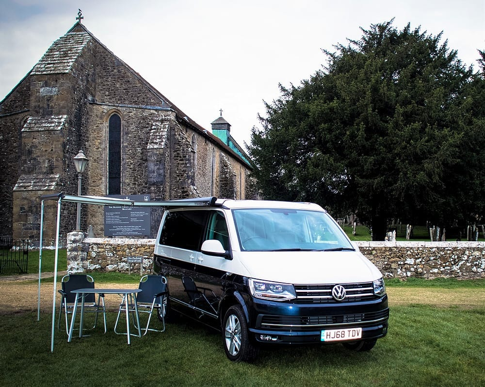 A VW campervan parked up infront of a church with a canopy and deck chairs.