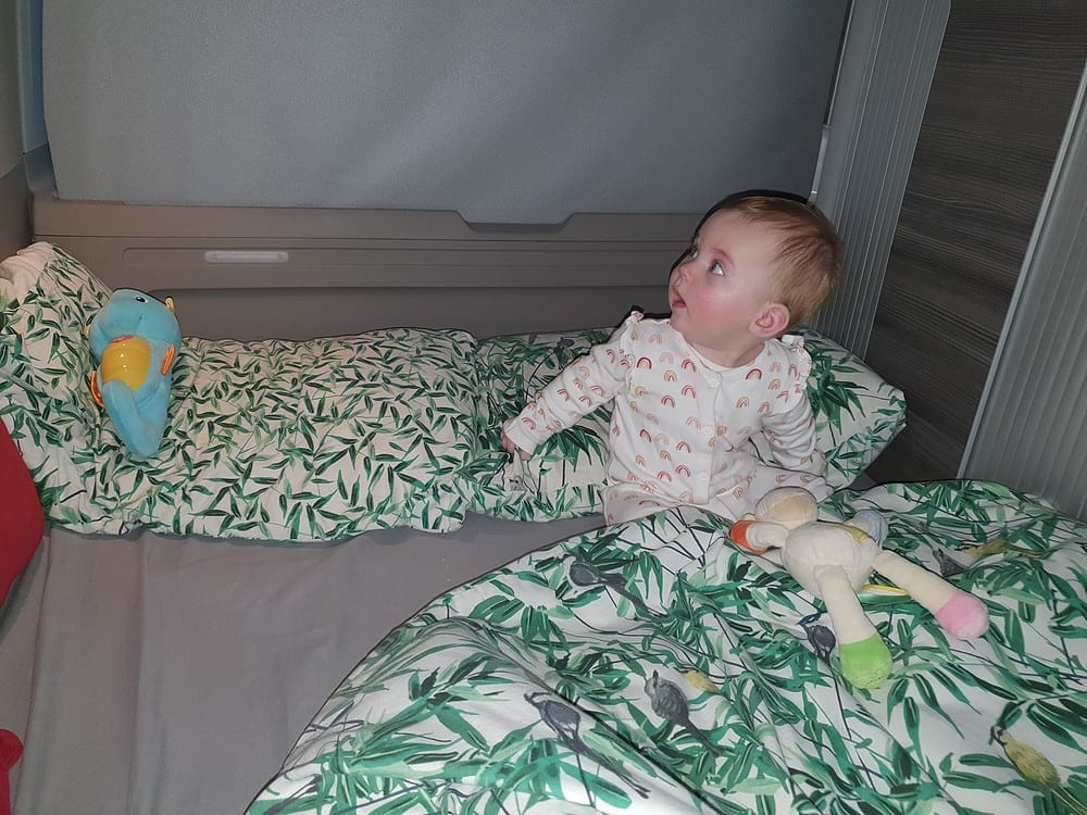 A baby playing with its toys inside a VW campervan bed.
