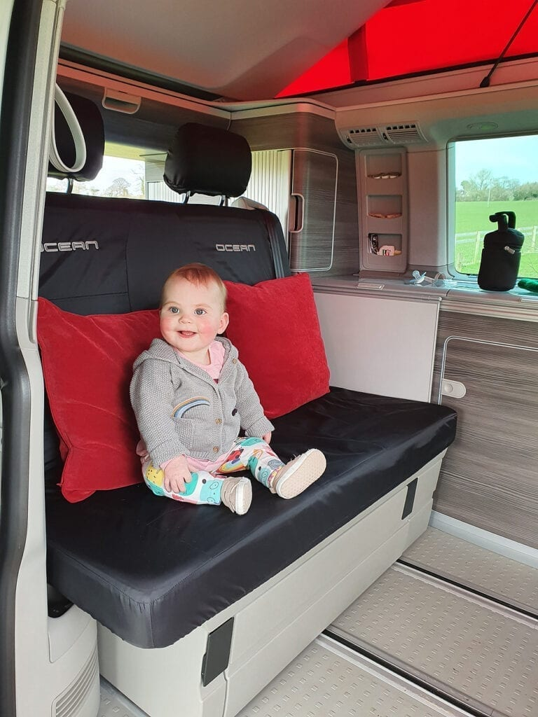 A photo of a baby enjoying their time in a VW campervan seat.