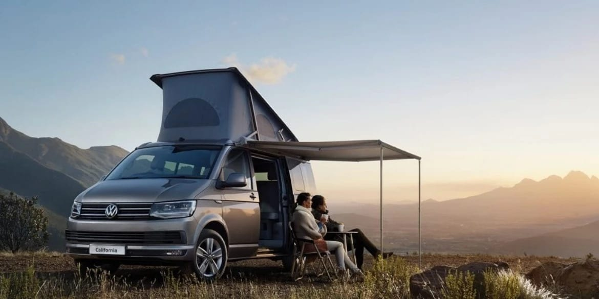 A VW campervan with a canopy extended out on a mountain range.