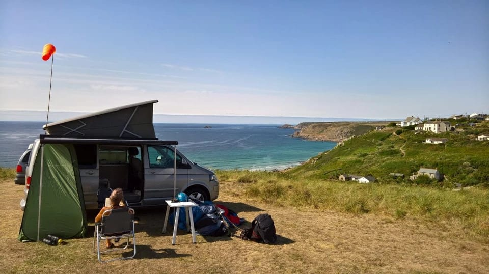 A VW campervan on top of a cliff.