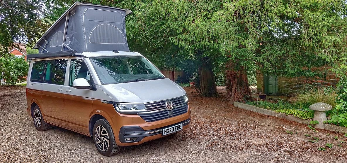 A two tone VW campervan for hire from Southampton, in a forest car park.