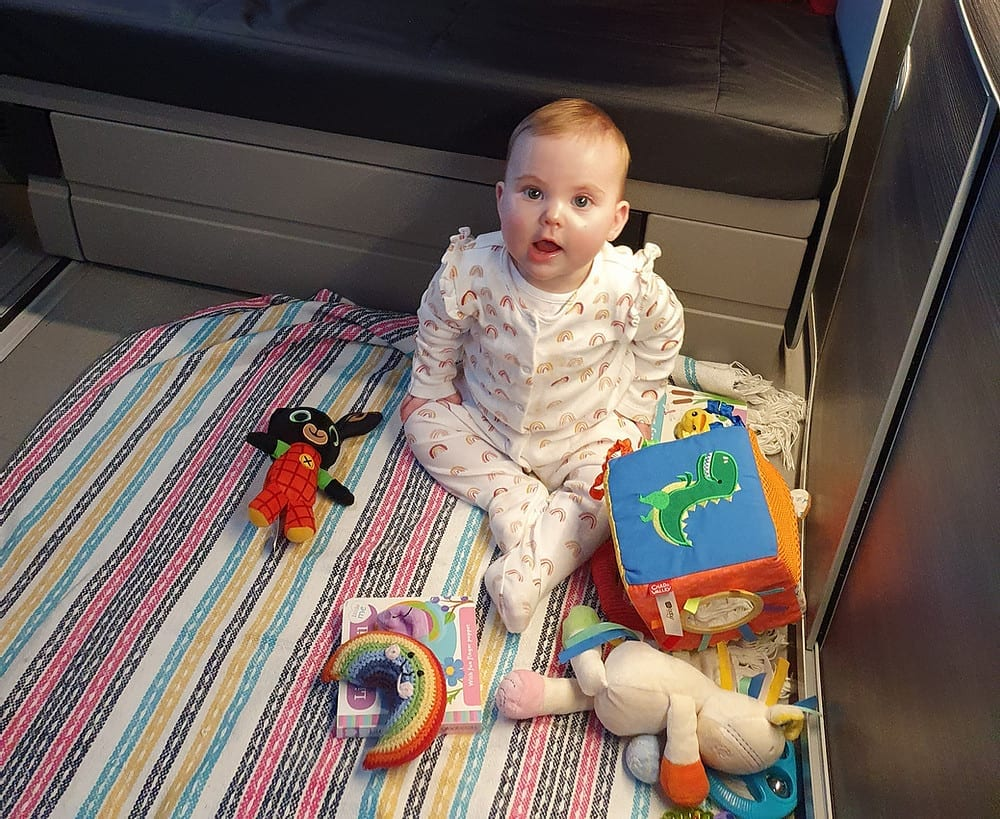A baby playing with their toys on the floor of a VW campervan