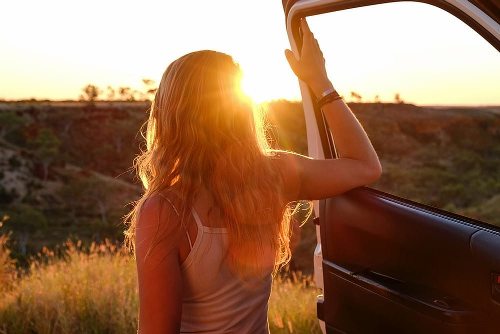 A woman standing and resting on the door of her VW campervan in the sunset.