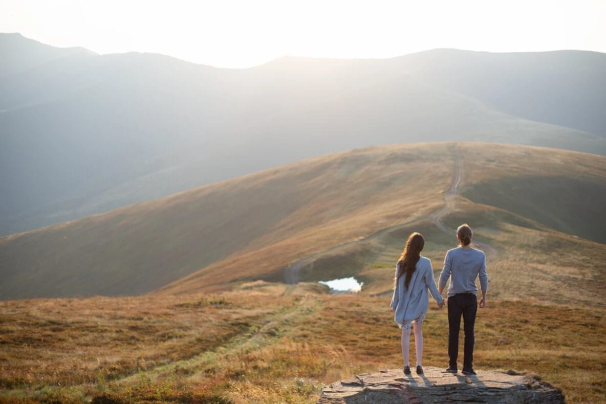 Two people holding hands at the top of a hill and mountain range.