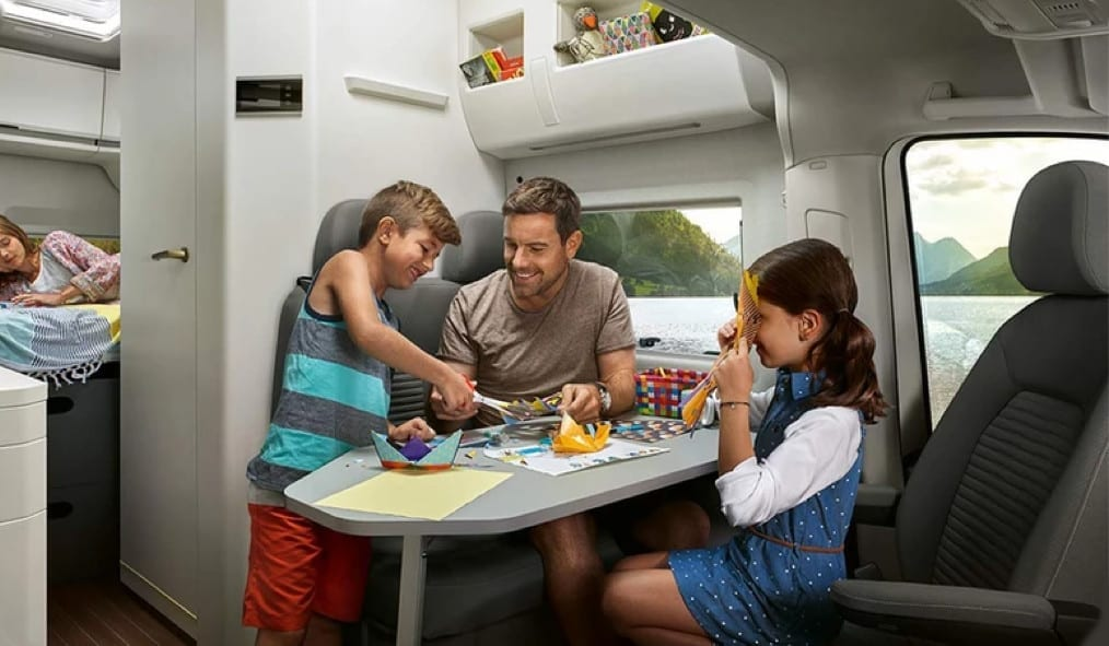 A father and 2 children eating around the pull out table inside of a VW Grand California.