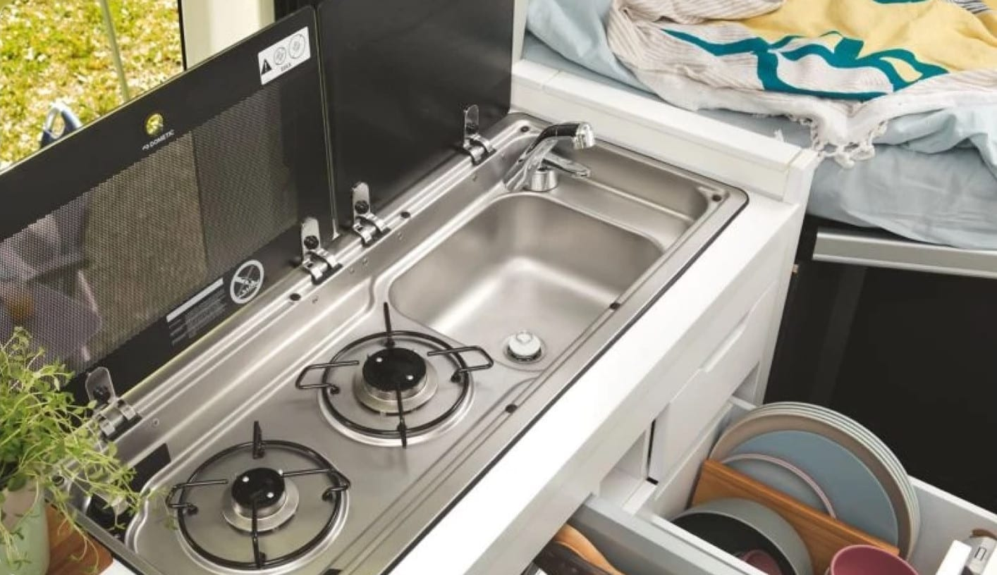 Photo of the cooker and sink installed inside of a VW Grand California.