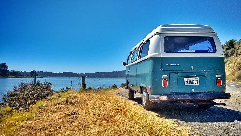 An old VW campervan parked up in front of a scenic lake view.