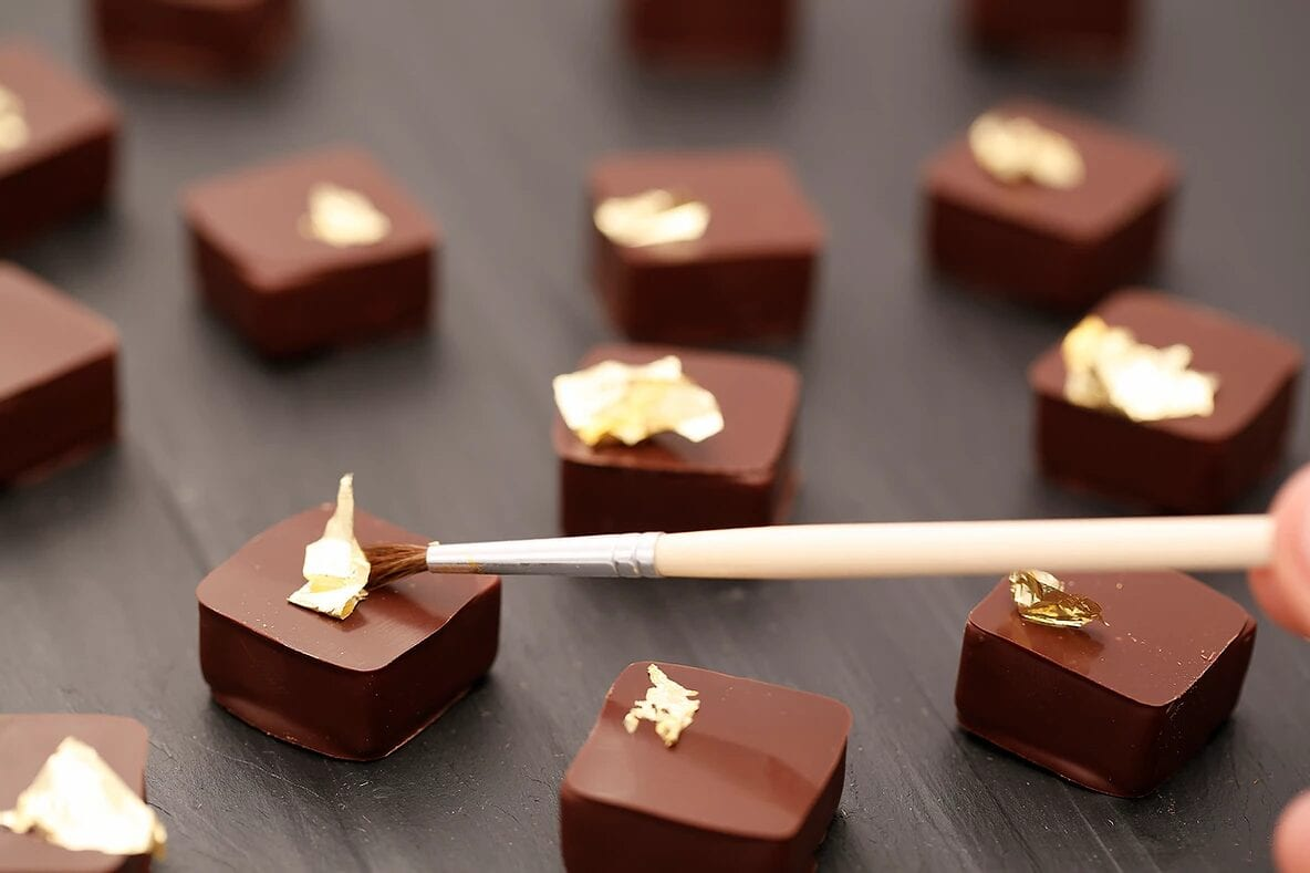 A close up photo of some fancy chocolates being painted gold.