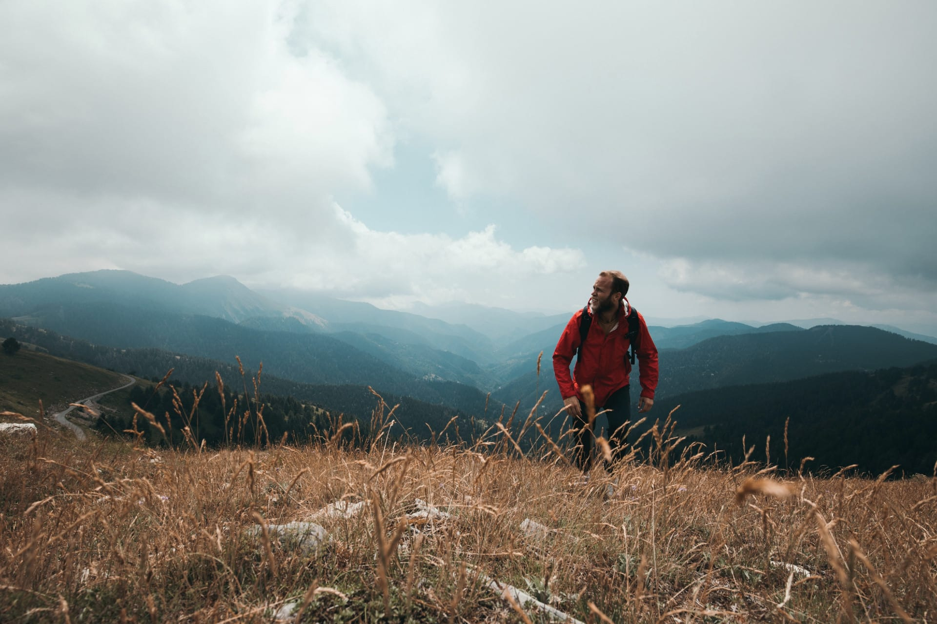 A man in a red coat, hiking up a mountain range.