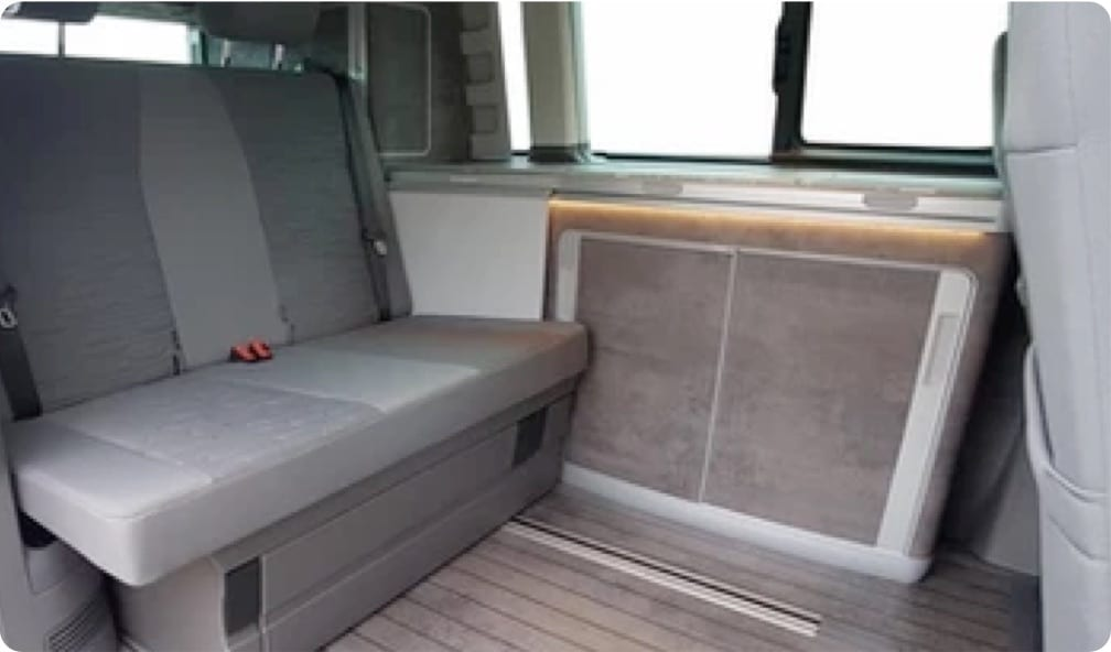 A photo of the rear seats and worktop inside of a VW campervan.