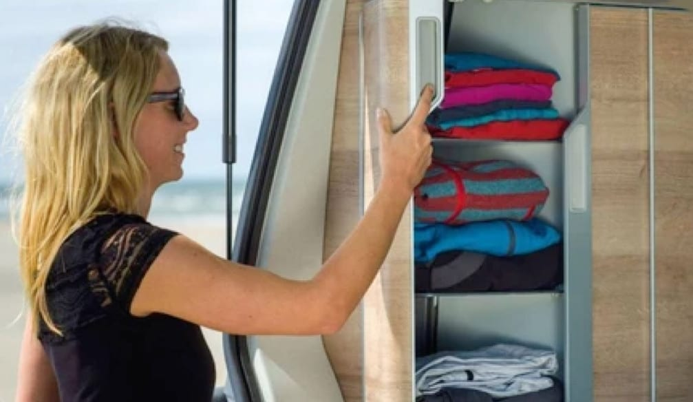 A woman using the storage space inside of a VW campervan.