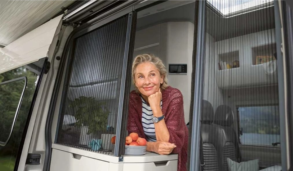 An elderly lady looking outside through a window of the campervan.