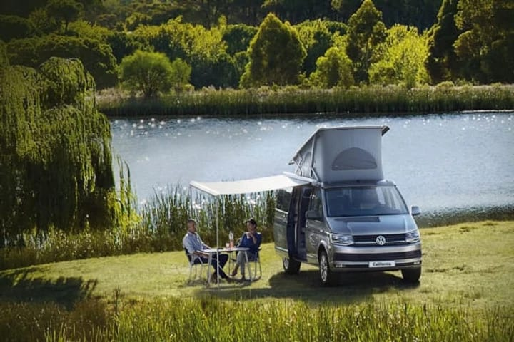 A man sitting in a camping chair, enjoying the view next to his VW campervan.