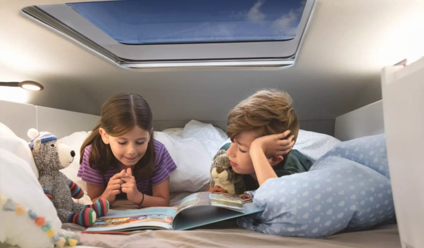 2 children led on a bed inside of a VW Grand California reading a magazine together.